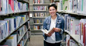 student in library holding a book and smiling