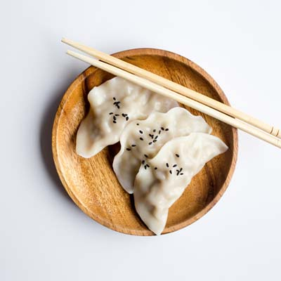 potstickers on a plate with chop sticks